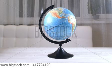 Globe Model Spinning On Wooden Desk. White Wall Empty Space Background: Moscow, Russia - February 25
