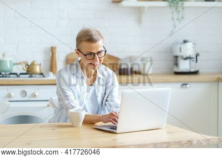 Modern Happy Mature Woman Wearing Glasses Working Or Studying On Laptop While Sitting In Kitchen At