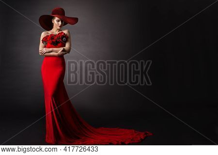 Woman Red Dress And Hat. Fashion Model In Long Evening Gown With Flowers. Black Studio Background.