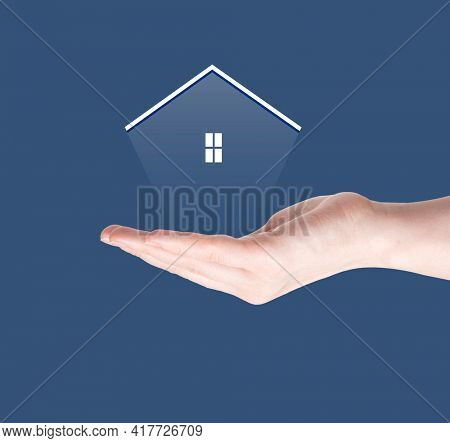Woman hand hold a transparent home model on sunlight, Saving for buy a new house or real estate and loan for plan business investment concept. Real estate concept