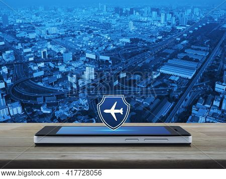 Airplane With Shield Flat Icon On Modern Smart Mobile Phone Screen On Wooden Table Over City Tower,