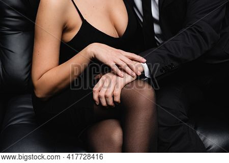 Cropped View Of Passionate Man In Suit Seducing Sexy Woman In Slip Dress Sitting On Sofa On Black.