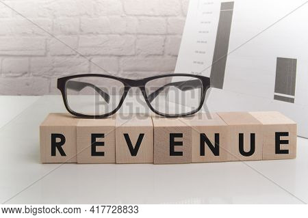 Word Revenue On Ascending Arrow Above Bar Graph Of Wooden Small Cubes Isolated On Black Background.