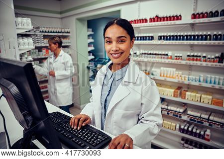 Portrait Of Smiling Young Female Pharmacist Wearing Labcoat Working On Computer In Drugstore Looking