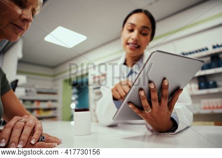 Closeup Of Young Female Pharmacist Hand Holding Digital Tablet Wearing Labcoat And Standing Behind C
