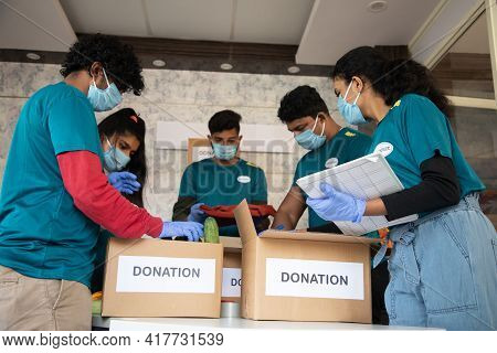 Low Angle View, Group Of Volunteers Busy Working By Arranging Vegetables And Clothes On Donation Box