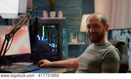 Streamer Man Looking At Camera Smiling While Streaming Videogames