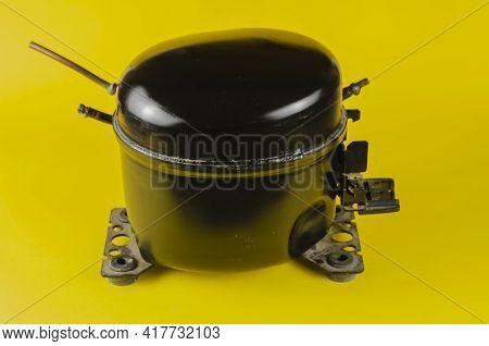 Black Refrigerator Motor-compressor On Yellow Background. Old Hermetic Piston Compressor. Device Des