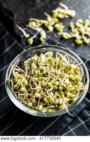 Sprouted green mung beans. Mung sprouts in bowl on black table.
