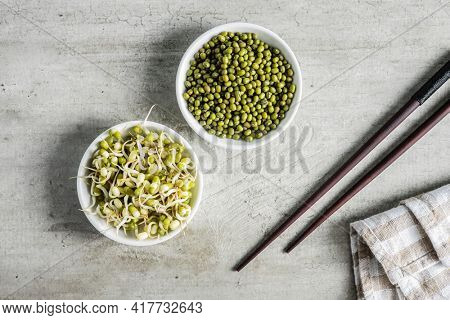 Sprouted green mung beans and dried beans in bowl. Mung sprouts on kitchen table.
