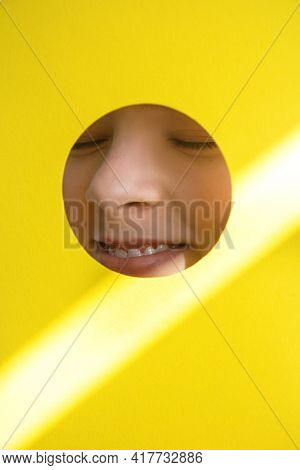 Beautiful Smiling Girl Face Looking Through Round Hole In Yellow Paper And Sunbeam