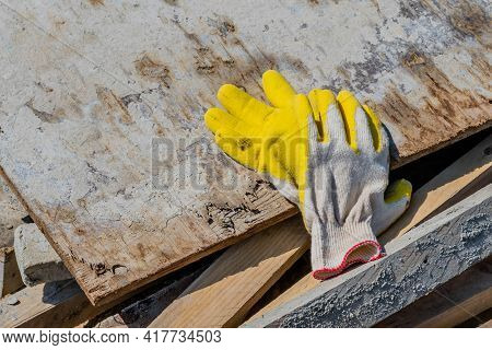 Pair Of Cotton Work Gloves Laying On Old Piece Of Plywood.