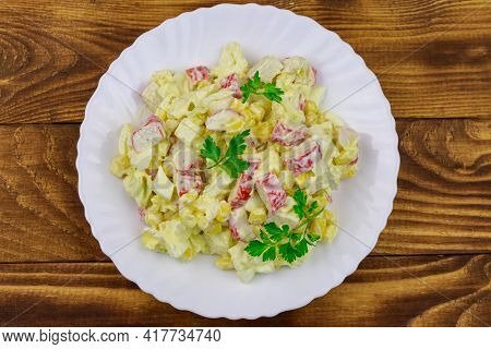 Salad With Crab Sticks, Sweet Corn, Chinese Cabbage, Eggs And Mayonnaise On Wooden Table