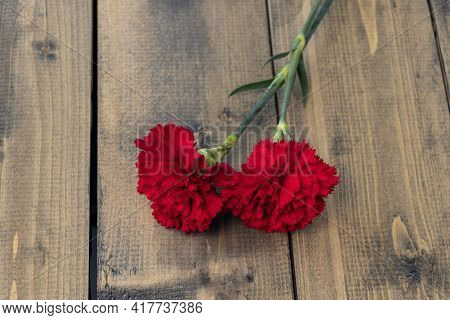 Two Red Carnations On A Wooden Background. Two Carnations As A Symbol Of Grief And Death. Soft Focus