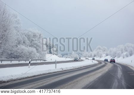 Complicated Driving Conditions In Winter. Snowy Road With The Cars.