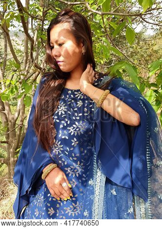 Photo Of A Beautiful Asian Young Girl Wearing Blue Dress And Touching Her Hair With Looking Down, Pe