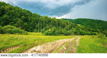 Dirt Road Through Forested Countryside. Beautiful Summer Rural Landscape In Mountains. Adventure In