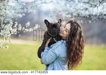 Beautiful Young Woman Playing With Bulldog Outdoors. Cute Hipster Girl Hugs And Kissed Her Dog.