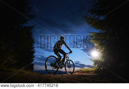 Back View Of Man Cyclist Riding Bike Under Blue Evening Sky With Clouds. Silhouette Of Bicyclist Rid