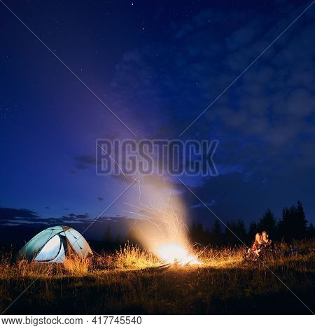 Night Sky With Stars And Clouds Over Grassy Hill With Illuminated Camp Tent, Campfire And Hikers. Yo