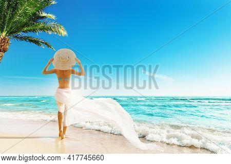 Woman Summer Beach Vacation. Travel Girl Sunbathing In Sun Hat, Bikini, White Fluttering Dress. Wome