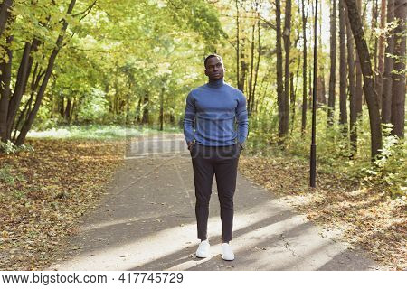 Positive African American Young Man In Stylish Clothes Walks In Late Summer Park On Sunny Warm Warm