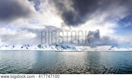 Panorama of snow covered mountains with low cloud. Golden sunlight at dusk. Svalbard, a Norwegian archipelago between mainland Norway and the North Pole