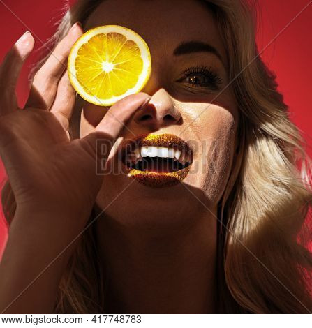 Portrait of young blonde woman holds slice of lemon