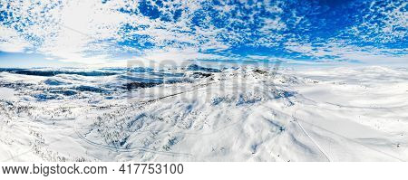 Stunning Panoramic View Over Snow Capped Arctic Mountains And Wilderness Terrain On A Clear Cold Win