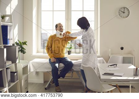 Doctor Examine Patient With Neck Cervical Collar In Rehabilitation Clinic Office