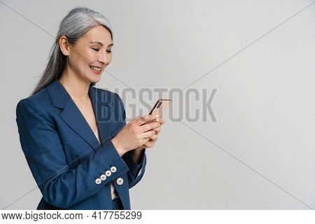 Asian mature woman in jacket smiling while using mobile phone isolated over white wall