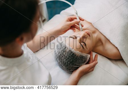 Upper View Photo Of A Caucasian Spa Worker Cleaning Clients Face With Apparatus During Skin Care Pro