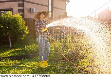 Happy Woman Gardener In Work Clothes Watering The Beds In Her Vegetable Garden On Sunny Warm Summer