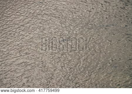 Monochrome Texture Of Golden Calm Water Of Lake. Meditative Ripples On Sunny Water Surface. Nature M