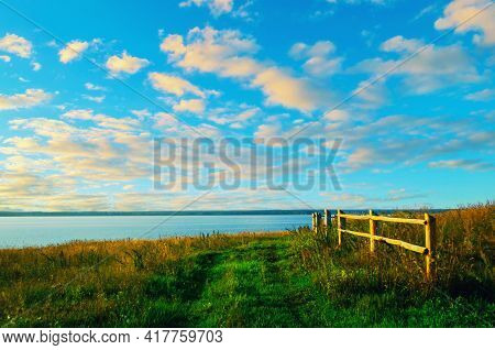 Summer landscape, summer field pathway along the summer lake, dramatic colorful summer sunset sky. Summer rural landscape, summer field nature, summer natural background, summer sunny landscape view. Summer landscape