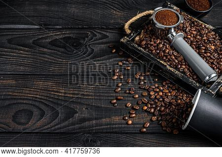 Ground Coffee In Portafilter For Espresso In A Wooden Tray With Coffee Beans. Black Wooden Backgroun