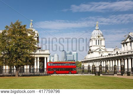 Red Double Decker Bus In A Central London Scene. The Old Royal Naval College And National Maritime M