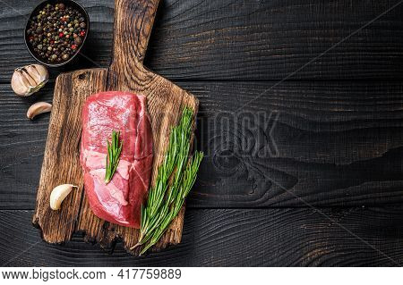 Fresh Raw Veal Sirloin Meat Steak On A Wooden Cutting Board. Black Wooden Background. Top View. Copy