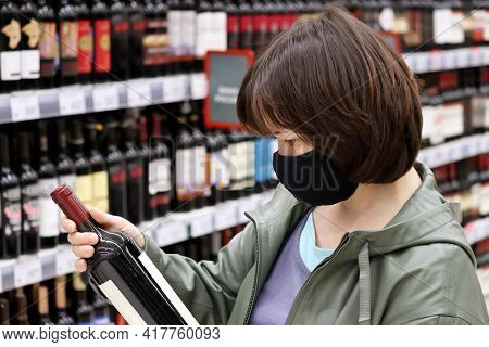 Woman In Medical Face Mask Reading The Label On Red Wine Bottle. Customer In Liquor Store, Concept O