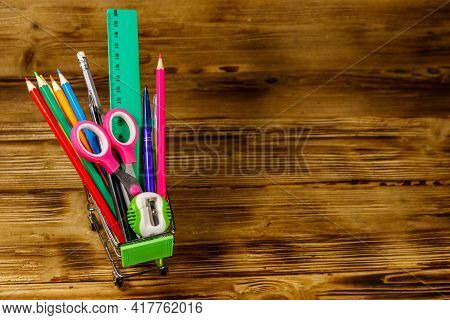 Buying School Supplies. Shopping Cart With School Supplies On A Wooden Background. Back To School Co