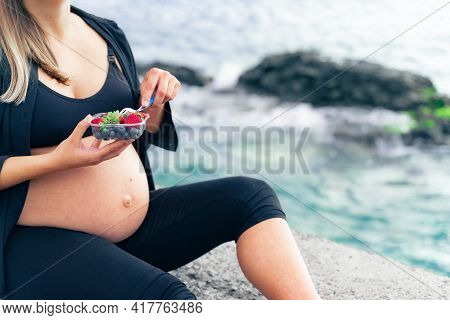 Pregnant Woman Sitting Near The Sea And Eating Fresh Fruit Salad, Closeup. Healthy Food And Love For