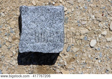 Gray Granite Cube Against A Background Of Yellow Sand And Small Stones. Square Stones For Sidewalks