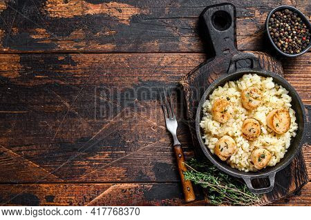 Seafood Risotto With Scallops In A Pan. Dark Wooden Background. Top View. Copy Space