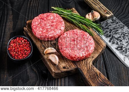 Raw Steak Cutlets With Mince Beef Meat And Rosemary On A Wooden Cutting Board With Meat Cleaver. Bla