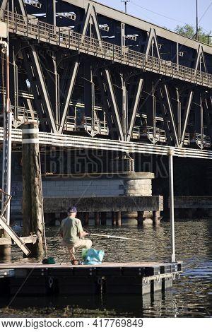 Sesto Calende (va), Italy - September 15, 2016: A Fisherman Near The Bridge Between Lombardy And Pie