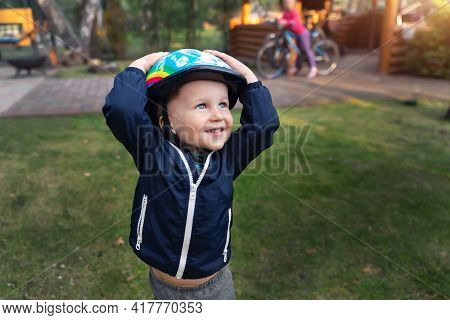 Cute Little Adorable Caucasian Happy Toddler Boy Put On Head Safety Helmet Going To Have Fun Riding