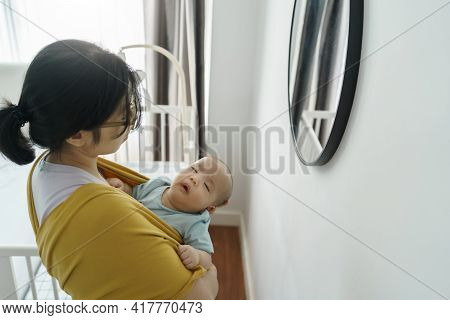 Loving Asian Young Mother Holding Her Little Sleeping Newborn Baby Son At Home. Caring Love, Care An