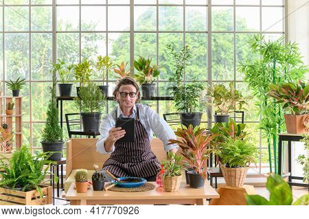 Happy Senior Man Gardening Wearing Glasses And Denim Apron With Digital Tablet Sitting In Home Garde