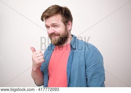 Dishonest Caucasian Man Points His Thumb To The Side And Looks Slyly. White Background.