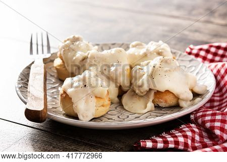 Traditional American Biscuits And Gravy For Breakfast On Wooden Table